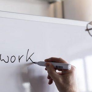 Thomas Schulte der Teamwork an eine Whiteboard zeichnet